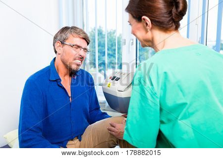 Orthopedist practitioner looking at knee of patient in doctors office