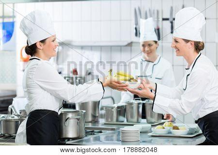 Kitchen brigade in catering kitchen preparing dishes