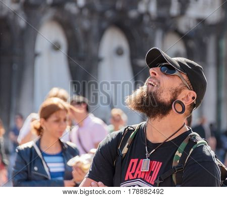 Venice Italy - September 28 2015 : The tourist is standing on San Marco Square and looks enthusiastically at Campanile di San Marco tower in Venice Italy