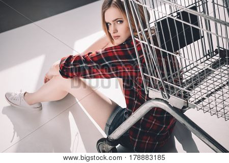 Attractive Young Woman Sitting Near Shopping Cart And Looking At Camera