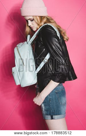 Side View Of Stylish Hipster Woman In Leather Jacket On Pink