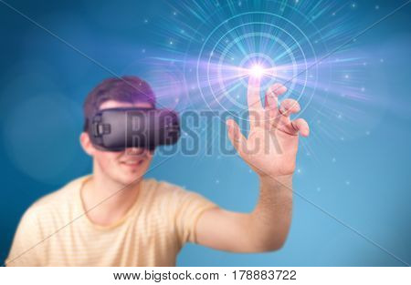 Young impressed man wearing virtual reality goggles with blue circles around his finger