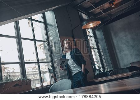 Thinking about solution. Thoughtful young man in smart casual wear keeping hand in pocket and looking away while leaning on the wall