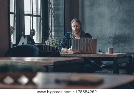 Little break during working day. Serious young man in smart casual wear keeping eyes closed while sitting at the office desk
