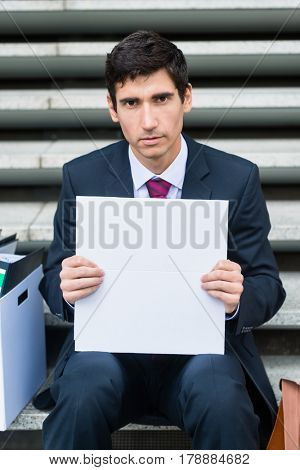 Portrait of young unemployed man showing blank whiteboard while sitting outdoors on stairs during economic recession