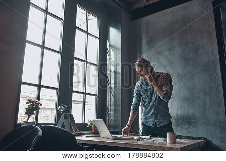 Developing new project using technologies. Serious young man talking on the mobile phone and working using laptop while standing near the office desk