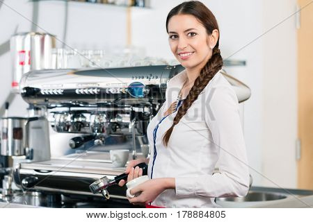 Portrait of young waitress smiling and looking at camera while standing near the automatic coffee machine