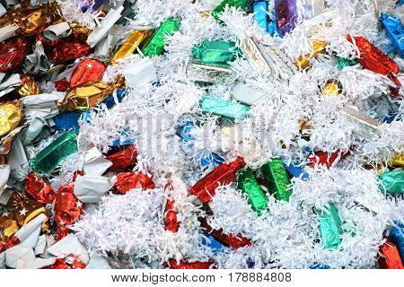 Hard candies in a pile, wrapped in colorful, glossy papers