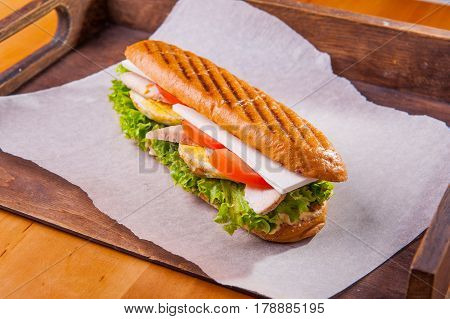 Ciabatta Chiken Sandwich With Lettuce, Slices Of Fresh Tomatos, Scrambled Eggs And Mozzarella Cheese