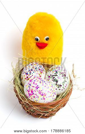 Coloured eggs, base and yellow chicken toy- the symbol of Easter
