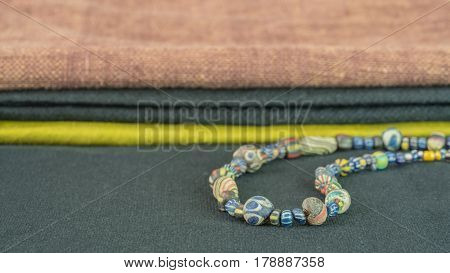 Close up on ancient rare variety of glass beads with variety of silk fabric backgroud