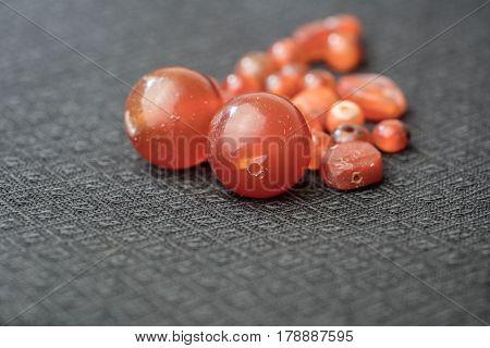 Varieties of ancient carnelian beads on Thai silk background