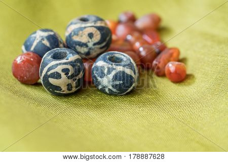 Ancient blue bird glass beads together with variety shapes of ancient carnelian beads on green silk cloth