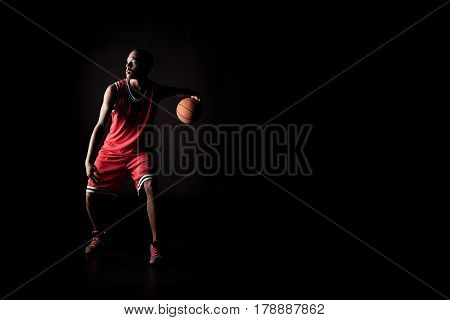 African Sporty Man In Sports Uniform Playing Basketball On Black