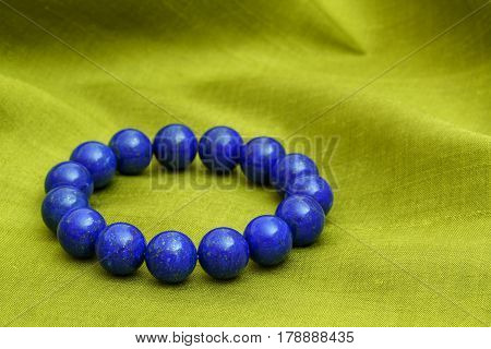 Beautiful high grade royal blue Lapis lazuli beads in bracelet on green Thai silk background