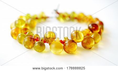 Ancient yellow glass button bracelet separated by small red trade beads on white background