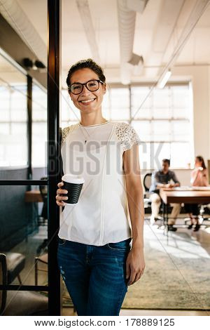 Portrait of smiling young woman standing in office doorway with coffee. Relaxed female executive having coffee break with colleagues working in background.
