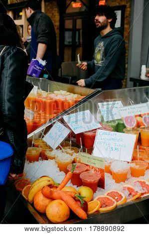 LONDON, UK - MARCH 18, 2017: Fresh juice market stall in Greenwich Market, London's only market set within a World Heritage Site.