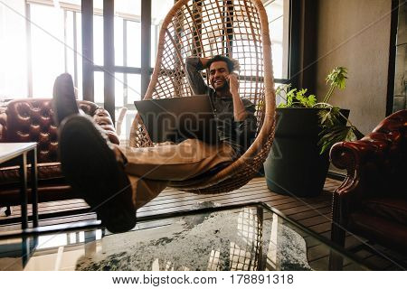 Happy young business man sitting on a wicker hanging chair in office lounge with laptop and talking on mobile phone. Male executive relaxing in office lounge during break.