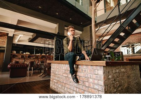 Creative young man sitting in office cafeteria with laptop and talking on mobile phone.