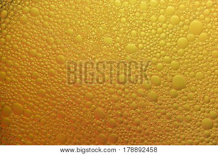 Abstract background of bubbles of foam colored gradient diagonally in yellow color