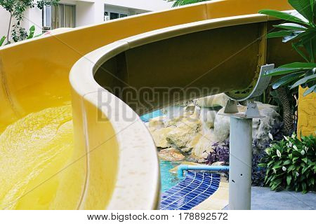 Closeup Swimming pool slider. Yellow swimming slider and abstract nature background