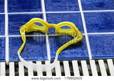Swimming glasses on floor at swimming pool. Swimming goggles