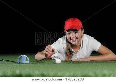 Young female golf player on artificial field at the mini golf club. The ball, the golf club and hole course are near a girl. Mini golf inside interior