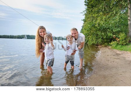 Happy family - father, mother, two sons on the beach with their feet in the water at sunset. They are all smiling, looking at the camera.