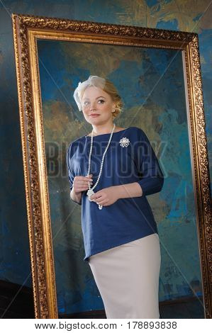 A mirror reflection of a beautiful woman. Mirror in a classical style. Three quarter length portrait in a studio.