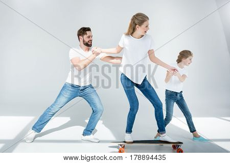 Happy Father And Daughter Helping Young Woman Riding Skateboard