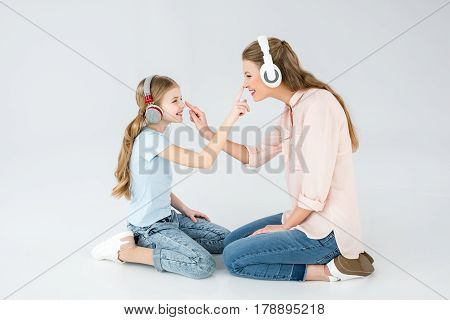 mother and daughter listening music with headphones in studio on white