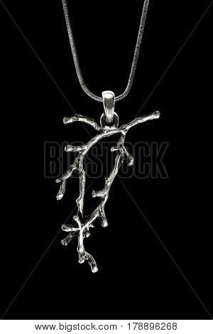 Silver pendant in the form of tree branch on black background