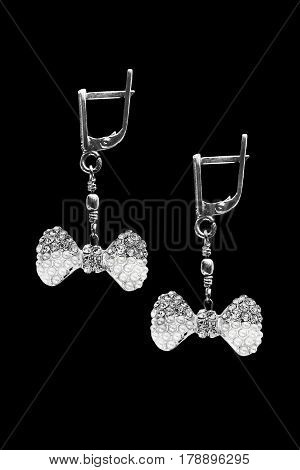Diamond and pearl earrings in the form of bows on black background