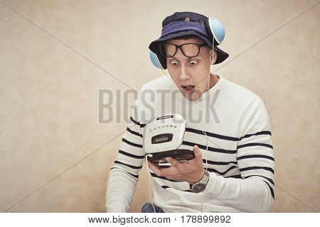 Shocked young man in panama looking at opened compact disk player