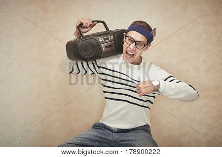 Portrait of funny cheerful man with boombox on his shoulder