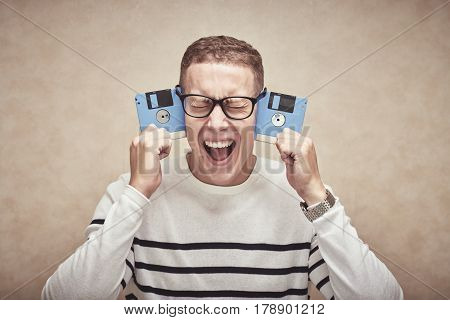 Young man holding two floppy disks near his head and shouting