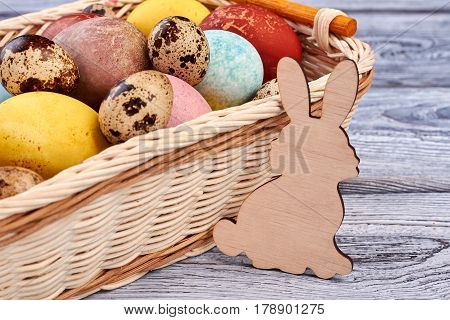 Easter basket and plywood rabbit. Animal cutout close up. Simple Easter crafts.