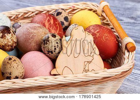 Plywood rabbits cutout and eggs. Woven basket close up.
