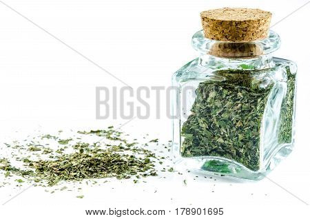 Dry parsley herb in glass bottle and heap near it isolated on white background. Closeup macro shot.