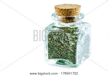 Dry parsley herb in glass bottle isolated on white background. Closeup macro shot.