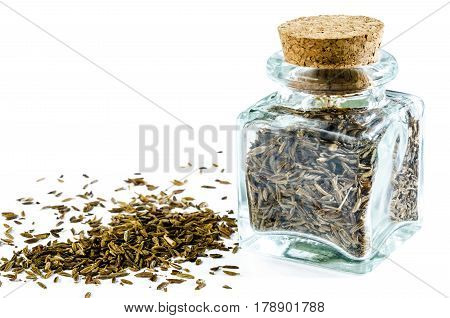 Dry cumin in glass bottle and heap of cumin isolated on white background. Closeup macro shot.