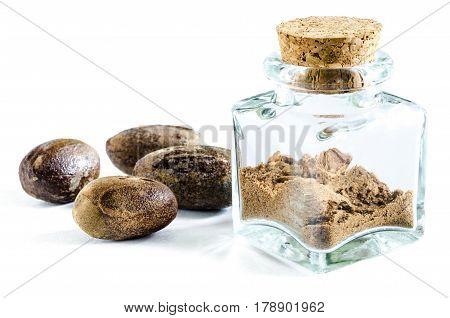Dry nutmeg powder in glass bottle and whole nutmeg near it isolated on white background. Closeup macro shot.