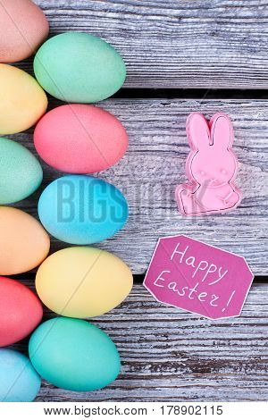 Vertical rows of colored eggs. Happy Easter card, plastic rabbit. New Easter merchandise.