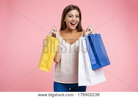 Closeup portrait of young smiling woman looking glad after good shopping isolated on pink background