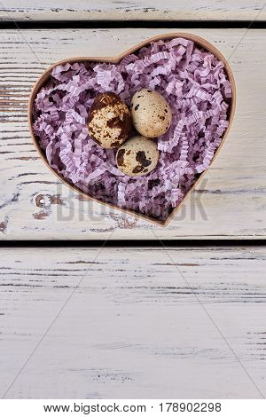 Heart shaped box, quail eggs. Present box on wooden background. The gift of life.