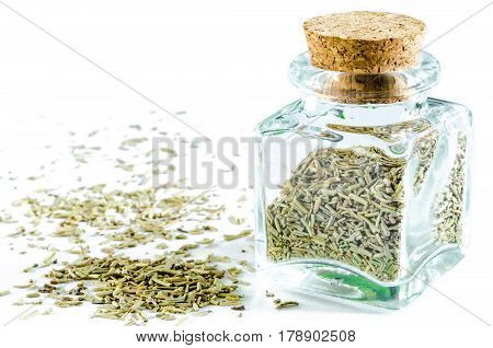 Dry rosemary in glass bottle and heap of rosemary isolated on white background. Closeup macro shot.