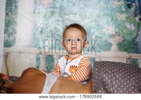 A pretty baby boy in a vest just woken up sitting on a bed with mother