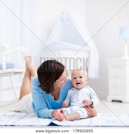 Happy young mother and adorable baby boy playing on a blue floor mat in a white sunny nursery with rocking chair and bassinet. Bedroom interior with infant crib. Mom and child on playmat at kids bed.