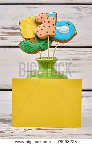 Easter cookies and blank card. Three colorful biscuits on sticks.